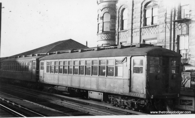 """Chicago Rapid Transit car 4293 at University on the Jackson Park """"L"""". If not for the sign on the platform, I would've hard a difficult time identifying this location. The car is flying American flags, which may mean this picture was taken on July 4th or some other holiday."""