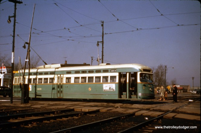 """CTA PCC 4169 (a Pullman) is eastbound at 119th Street, near the south end of Route 36 - Broadway-State, as it crosses over the Pennsylvania Railroad's """"Panhandle"""" route."""