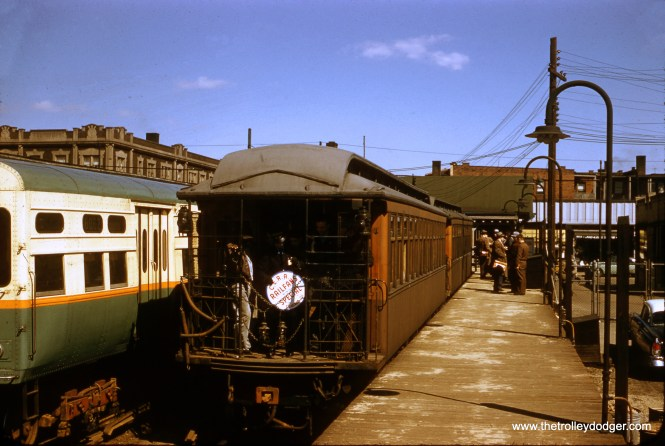 """CTA gate car 390 is part of a two-car Central Electric Railfans' Association fantrip train at the Ravenswood terminal at Kimball and Lawrence in April 1957. Note the original station entrance, then nearly 50 years old, which had a green roof at this time. Sean Hunnicutt: """"That is 6062 on the left."""""""