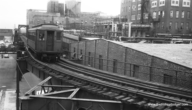 "I was very fortunate to purchase this 1950s negative showing the CTA Stock Yards branch. Daniel Adams: ""The view is facing east, at the intersection of Exchange and Packers Avenues. Racine Avenue Station, the first station encountered when a train consist pulls into the famed Stock Yards loop, can be seen in the distance. This train is beginning to make the first curve of the loop, to be heading south and soon pulling into Packers Station, which just a short distance away. Way back in the background, we can see the rather hazy tower of the Stock Yards National Bank, which stood on the west side of South Halsted Street."" Andre Kristopans notes, ""A correction re Stock Yards - the first station on the loop was Racine, the second SWIFT, then Packers, then Armour."" So this train is between Racine and Swift."