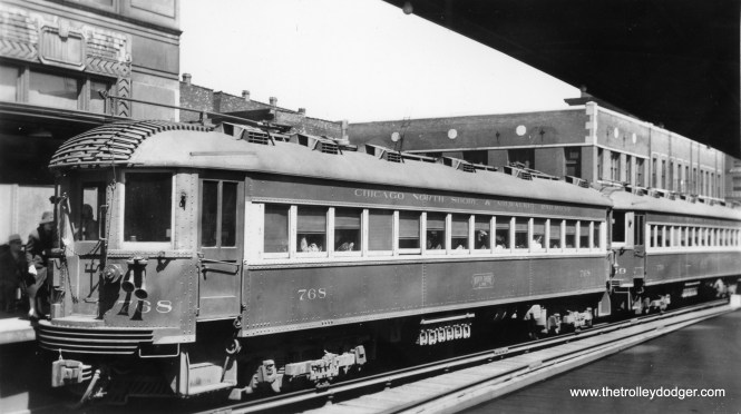 "This is the third ""L"" photo I have, taken at this location, which at first was a mystery, but eventually turned out to be an annex (since demolished) just north of the Merchandise Mart.  All three photos may have been taken at the same time, and by the same photographer, in the 1930s.  This one shows North Shore Line cars 768 and 769."