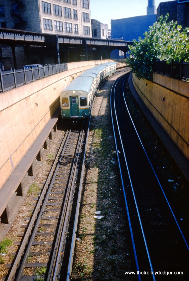 "On August 15, 1954, a four-car CTA train of 6000s heads northbound into the State Street Subway at the south portal at 13th and State. The section of ""L"" to the left was then not being used by CTA trains on a regular basis. Now the situation is reversed-- the ""L"" is used by regular trains, but the subway portal is not, since Howard trains are connected to the Dan Ryan line via a different tunnel. (William C. Hoffman Photo)"