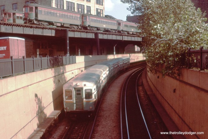 "On August 24, 1958, we are looking to the southeast at the State Street Subway's south portal at 13th and State. A northbound CTA train heads into the tunnel, while North Shore Line cars are sitting up on the nearby ""L"". Between 1949 and the 1963 abandonment, NSL trains had exclusive use of the Roosevelt Road ""L"" station, just north of here, and used the nearby tracks for storage. Now, those tracks are used by the CTA Green Line, while this subway portal only sees use when Red Line trains are diverted to the ""L"". (William C. Hoffman Photo)"