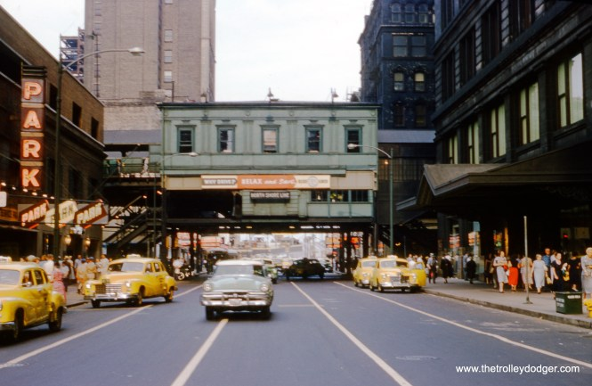 "When Bill Hoffman tool this picture on August 7, 1954, looking east along Randolph Street at the ""L"" station on Wabash, it was about to be renovated with, among other things, a large metal CTA logo and a new waiting room. The new station opened in 1957 and included a direct entrance to the second floor of Marshall Field's. Randolph and Wabash was replaced by a new station at Washington and Wabash (which also replaced Madison) in 2017. This picture is a bit blurry, probably because Hoffman had only a few seconds to take it before getting out of the way from oncoming traffic. I guess you could call it a ""grabshot."""