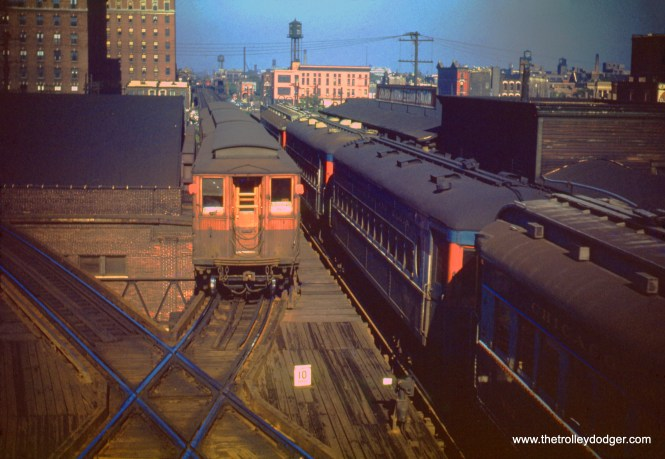 "On July 21, 1950, a CTA Grafield Park ""L"" train approaches Marshfield from the west, while a westbound Chicago Aurora & Elgin train is at the station. The tracks curving off to the left are for the Douglas Park branch (today's Pink Line), (William C. Hoffman Photo)"