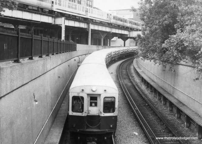 """A northbound Jackson Park-Howard """"B: train descends into the State Street Subway sometime in the 1970s. A Lake-Dan Ryan train, made up of 2000s and 2200s, is on the nearby """"L"""" structure."""