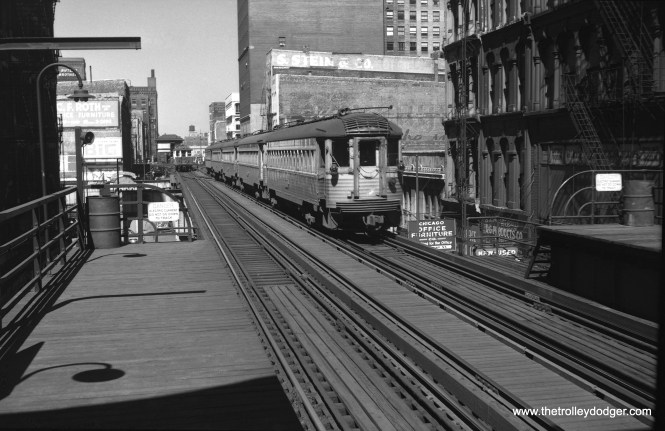 """A view looking west along the Lake Street """"L"""" sometime during the 1950s. The """"L"""" ran in one direction then (counter-clockwise), so both the """"L"""" train and North Shore Line train are heading west, away from the photographer. That's Tower 18 behind the train of 4000s, before it was replaced in 1969."""