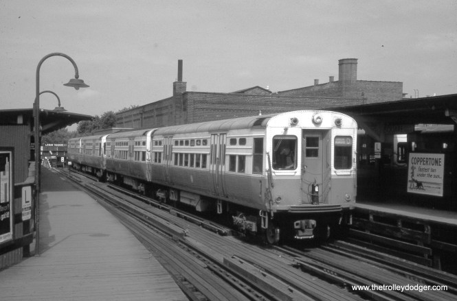 """In August 1963, a four-car Douglas-Milwaukee """"B"""" train prepares to leave Logan Square terminal.  Until 1970, this was as far into the northwest side of the city that """"L"""" service went.  By 1984, the """"L"""" had been extended all the way to O'Hare airport.  This train sports a fire extinguisher on its front, a practice that did not last, apparently because some of them were stolen.  While this elevated station was replaced by a nearby subway, the building underneath the """"L"""" actually still exists, although it has been so heavily modified that you would never know it is the same structure.  The Logan Square terminal was always my favorite """"L"""" station when I was a kid."""
