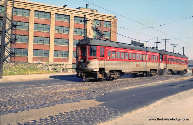 """A two-car train of North Shore Line Silverliners in Milwaukee in 1962. Larry Sakar writes: """"The train is northbound at the north end of the 6th Street viaduct (which no longer exists). Below it on the right of the train is what was then Fowler Street. Today, that is St. Paul Ave which in NSL days used to end at 6th St. All of that changed when The Milwaukee Road built their new station at 5th St. Impending construction of the Marquette interchange and the end of the Milwaukee Road's 4th & everett St. station gave the city the opportunity to continue St. Paul Ave. beneath 6th St. to connect with then Fowler St. which then became the continuation of W. St. Paul Ave. The warehouse next to the train is also long gone. If you were standing here today you would be looking at the Milwaukee Intermodal station on the right and the main Post Office immediately next door east. If you look two blocks down on the left that is where the present day HOP Streetcar terminates. The train is northbound at the north end of the 6th Street viaduct (which no longer exists). Below it on the right of the train is what was then Fowler Street. Today, that is St. Paul Ave which in NSL days used to end at 6th St. All of that changed when The Milwaukee Road built their new station at 5th St. Impending construction of the Marquette interchange and the end of the Milwaukee Road's 4th & everett St. station gave the city the opportunity to continue St. Paul Ave. beneath 6th St. to connect with then Fowler St. which then became the continuation of W. St. Paul Ave. The warehouse next to the train is also long gone. If you were standing here today you would be looking at the Milwaukee Intermodal station on the right and the main Post Office immediately next door east. If you look two blocks down on the left that is where the present day HOP Streetcar terminates."""""""