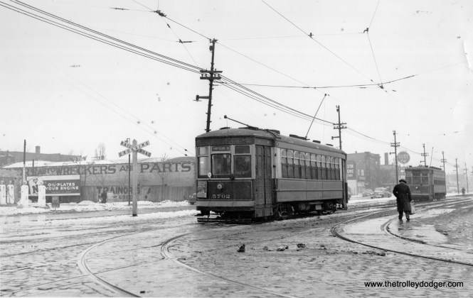 """CSL 5702, signed for 93rd and Stony Island. Our resident south side expert M. E. writes: """"I'm going to hazard a guess as to where this picture was taken. But first, I present my case. The destination sign on the first car says """"Stony Island-93rd""""; the sign on the second car says (I think) """"Stony Island-Downtown"""" -- yet both cars are on the same track, heading in the same direction. Why would that happen? It might happen if these were special fan trips, one car following the other, oblivious to their destination signs. Or it might simply be two Stony Island cars heading to 93rd St., but the sign on the second car is wrong. Another factor to consider is that the tracks on Stony Island ran in the street south to 69th St., but south of 69th, they had their own right-of-way between the north- and south-bound auto traffic lanes. In this picture, I believe I see a separation between the tracks and the car lane. Therefore this picture was taken south of 69th St. But the best clue, by far, is the round sign in the distance: """"Ruby OK used cars."""" The dealership was Ruby Chevrolet. I went to Google and looked up """"ruby chevrolet used car location south side chicago"""". Up came a link to a Tribune obituary about Richard Ruby, car dealer and attorney, dated 8 December 2014. In that obituary, it says Ruby's lot was at 72nd and Stony Island. Next, consider the railroad crossing sign. It is a dinky sign with no flashing lights. That would indicate a crossing that was lightly used by trains. I submit that this is the trackage used by the Baltimore and Ohio railroad that started at about 71st and Dorchester (as an offshoot from the Illinois Central main line), then ran southeast, along the ground, through South Shore and to the South Chicago neighborhood. In Google maps, if you enter """"73rd and Stony Island Chicago"""", you will see the path used by that trackage. It crossed Stony Island just south of 73rd. (This railroad trackage lasted a long time, because the B&O did not want to give it u"""