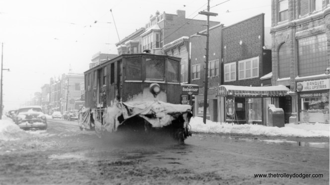 """Not sure which CTA snow plow this is. (Joe L. Diaz Photo) Bill Wasik says this """"shows an eastbound snowplow on 92nd St. as it approaches Baltimore Avenue. Can't identify the plow, but two buildings of note in this photo are still standing. These include the glass-bricked neo-Romanesque banquet hall at the far right. This is an 1891 corner block at the northwest corner of Baltimore Ave. Also visible one block to the west is a bank building that once was the headquarters of the Steel City National Bank, a facility mired in scandal during the early 1970s."""""""