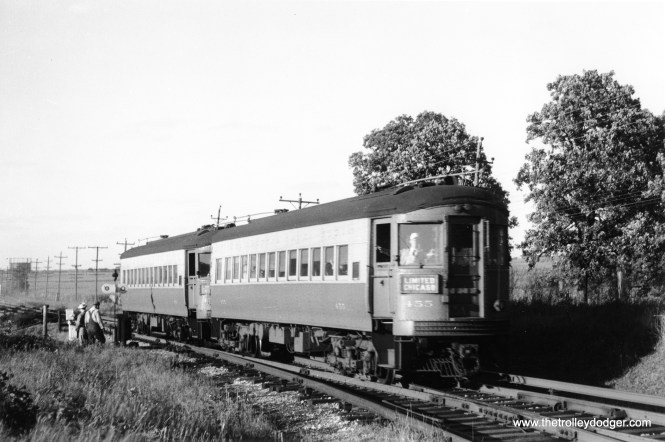 CA&E 455 at the front of a Chicago Limited. Not sure what the workers at left are doing.