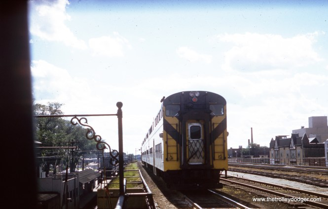 """A westbound Chicago & North Western commuter train departs from Oak Park in July 1960. Note the ground-level Lake Street """"L"""" station at Marion Street at left. Just over two years later, the """"L"""" was moved to this embankment. (William Shapotkin Collection)"""