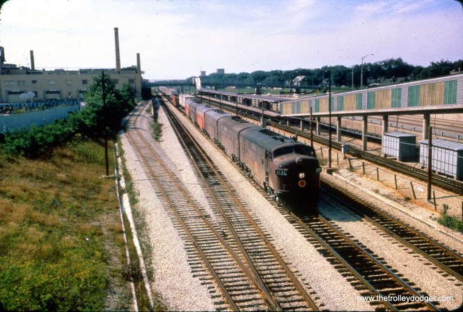 """A Chicago Great Western """"piggyback"""" freight train on Baltimore & Ohio Chicago Terminal tracks on September 13, 1965. The CGW was abandoned in the 1970s. We are looking west from Harlem Avenue in Forest Park, IL, with the CTA Congress rapid transit station at right (part of today's Blue Line). Note how the fiberglass panels on the ramp are arranged in a colorful pattern. Some years later, many of these were removed after some riders were robbed in these secluded walkways. (Dick Talbott Photo)"""