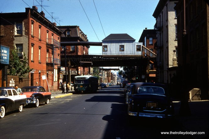 This is the Franklin Avenue station on the NYCTA-BMT Myrtle Avenue elevated in Brooklyn on June 14, 1958, with trolley bus 3039 running on Route 48 - Lorimer Street. Trolley buses were replaced by diesels in 1960, and the Myrtle Avenue El was closed on October 4, 1969. It was the last place on the New York system that used wooden cars. this was nearly 12 years after they were last used in Chicago. The El here opened in 1885, but the station you see here is not the original, but a more modern (and cheaply built) replacement. NY decided that upgrading this El would be too costly, so they got rid of it without replacement. Note the cool 1950s two-toned cars.
