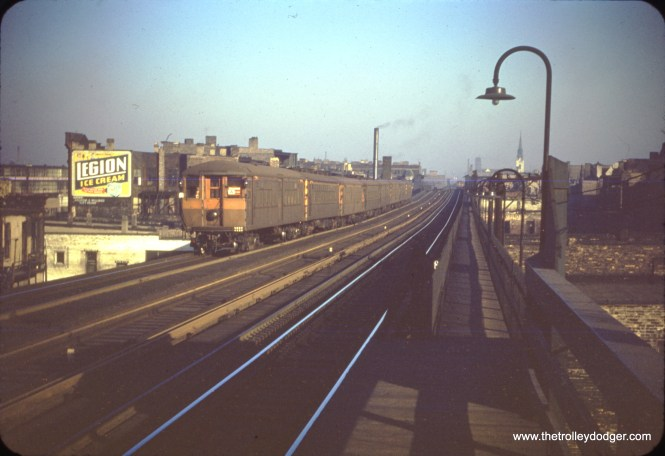 """An 8-car train of CTA 4000s, still in the old tan color, approaches 35th Street on November 6, 1950. In this somewhat underxposed slide, you can still make out the long walkway at right, which connected to a stairway at the former 33rd Street """"L"""" station, only used as an auxiliary entrance and exit for 35th after 1949. This walkway was closed on September 25, 1961 and removed thereafter. (William C. Hoffman Photo)"""
