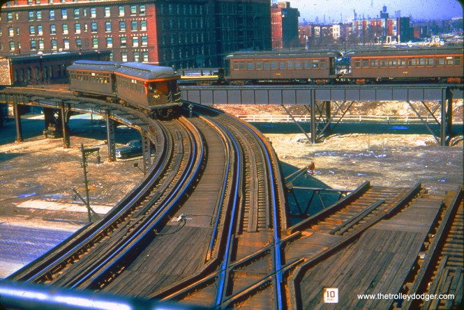 """A CTA train of 6000s is turning onto the Metropolitan main line from the Douglas Park """"L"""" on April 3, 1954, while a CTA test train (with car 2276) is on the new, as yet unused connecting track between the Douglas """"L"""" and the old Logan Square branch. Once Douglas trains began using this new """"L"""" connection, they began running downtown via the Lake Street """"L"""", and portions of the old """"L"""" east of here were torn down for expressway construction. By 1958, there was a new ramp in place, approximately in the same place the 6000s are here, leading down to the Congress rapid transit line in the expressway median. (Truman Hefner Photo)"""