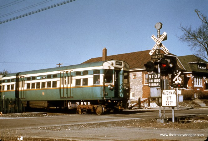 """CTA 6056-6057 crossing East Avenue in Berwyn, where a sign indicates that the crossing guard is off duty. This portion of """"L"""" was abandoned in February 1952. (Truman Hefner Photo)"""