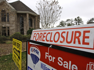 Bank repo, foreclosure and for sale signs sit outside a foreclosed home in Houston. (AP File)