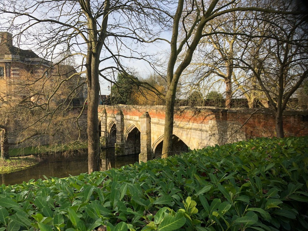Main entrance to Eltham palace across a medieval stone bridge