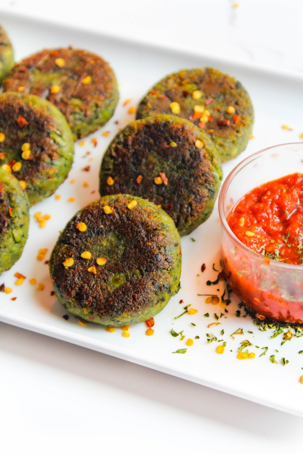 Green and brown spinach and pea kebabs / fritters / tikki on a white plate