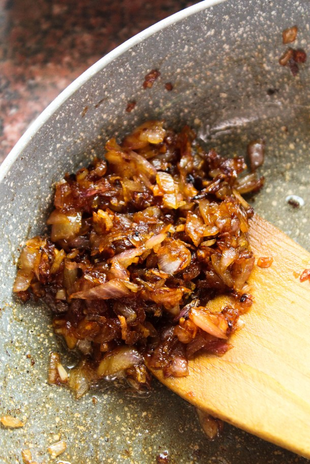 Golden brownglossy caramelized onions in a pan with a brown wooden spoon