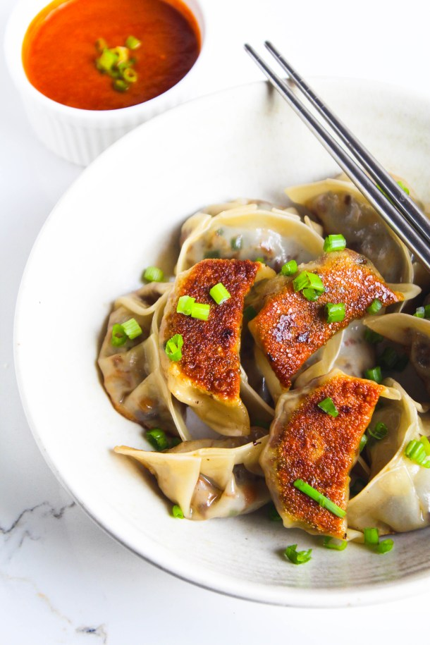 Pan fried mushroom potstickers (dimsums/ dumplings/ gyozas) on a white plate with green spring onions sprinkled on them served with a red sauce.