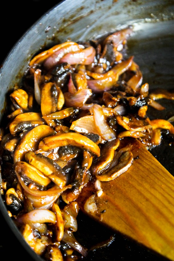 black brown mushrooms tossed in an asian sauce in a black pan with a brown wooden spoon