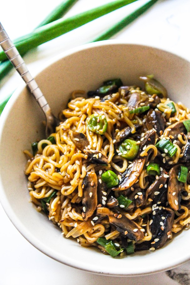 Ramen or maggi noodles tossed in a spicy asian brown sauce with some black brown mushrooms topped over them. Placed in a white bowl over a white tile. White Sesame seeds and green spring onion topping.