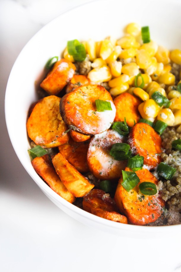 red orange roasted (oven baked) sweet potatoes and yellow corn with quinoa and a white salad dressing made with yogurt - in a white bowl over a white tile