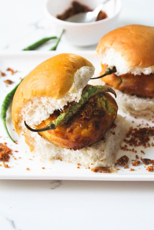 Deep fried golden brown potato vadas over pav bread and some red chilli, garlic and peanut chutney, plus a fried green chilli