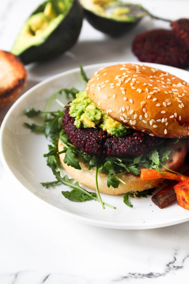 golden brown burger buns and green avocado smashed over pink / purple beetroot quinoa patties with green fresh arugula leaves on a white plate on a white tile