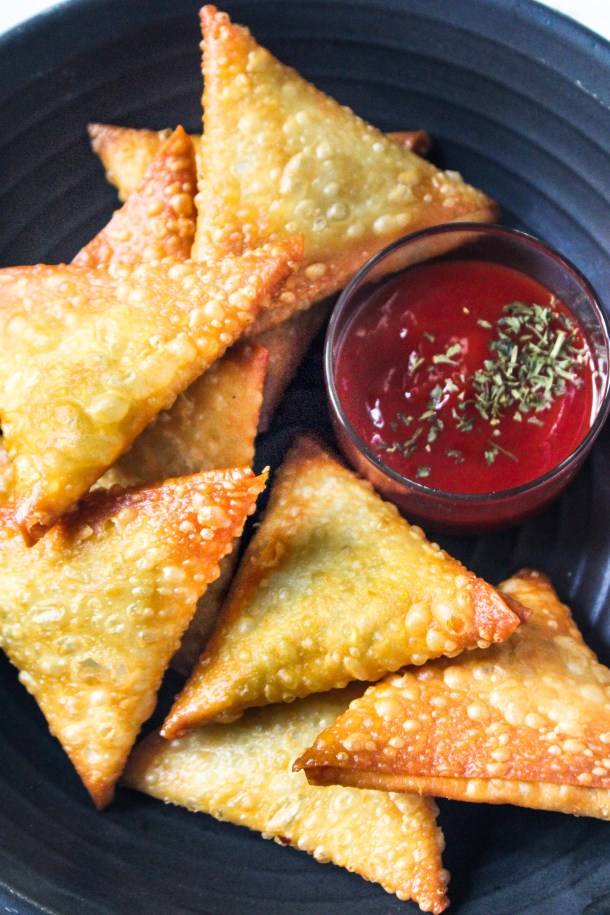 Golden brown crunchy mushroom and cheese samosas on a black plate with green parsley sprinkled on it, placed on a white tile. Served with red tomato ketchup.
