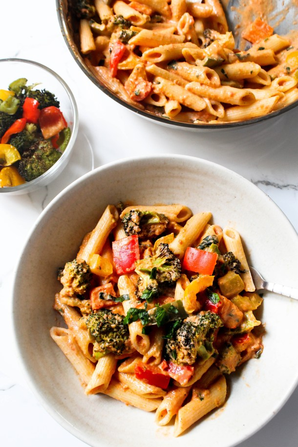 Red / orange / pink pasta sauce covered penne pasta with oven roasted broccoli, red, yellow and green bell pepper (capsicum) and green basil and parsley leaves in a stainless steel pan