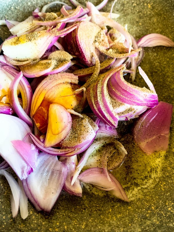 Thin sliced onions in a pan with some melted butter, honey, salt and pepper ready to be caramelized.