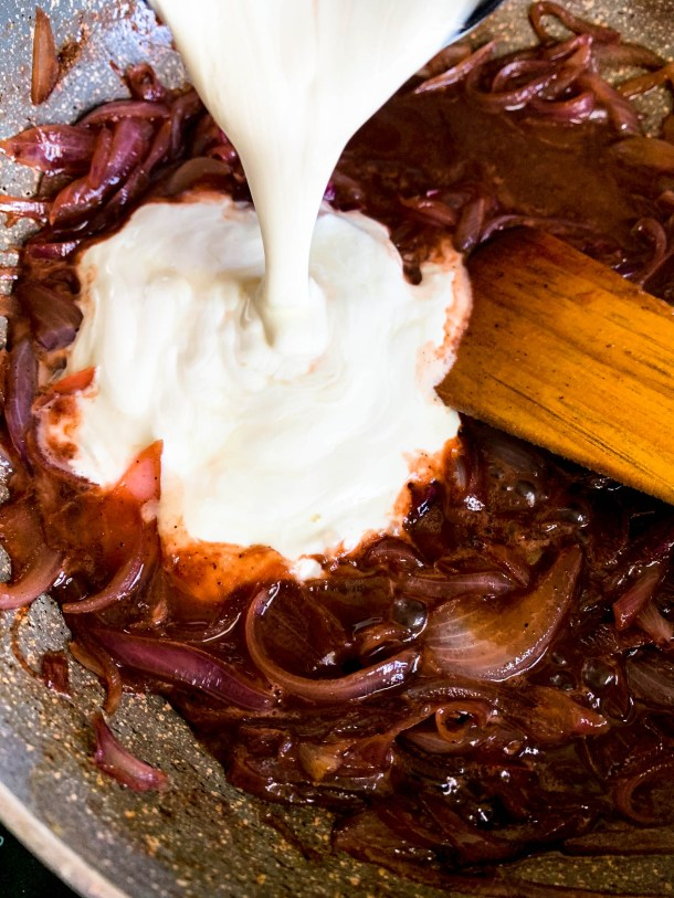 Thin sliced onions in a pan with some melted butter, honey, salt and pepper ready to be caramelized. White whipping cream being poured over it.