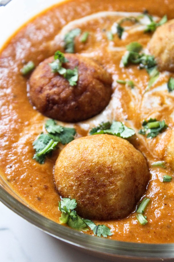 Orange Indian gravy (curry) with fried golden brown kofta (potato dumpling with indian cottage cheese) garnished with green coriander and cream, served in a glass casserole over a white tile.