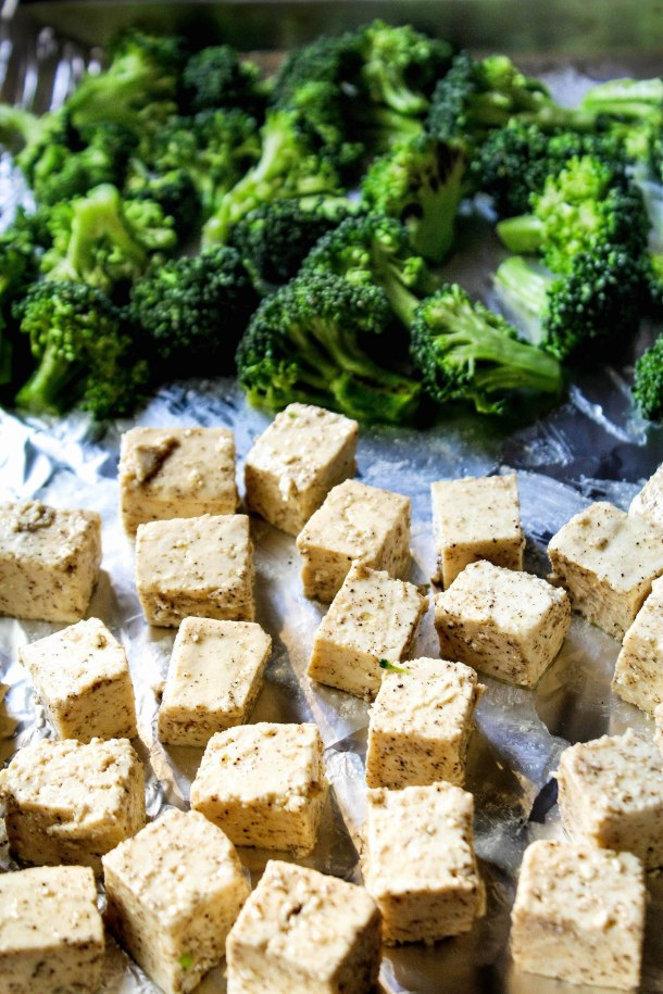 Oven baked cubed tofu tossed in a brown red spicy peanut butter sauce topped with white sesame seeds. Serve with rie and grilled / baked broccoli. Placed in a white bowl over a white tile.