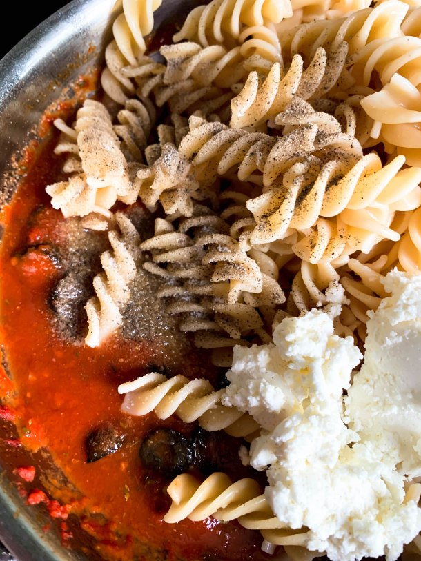 Butter, garlic, black olives, starchy pasta water, fusilli pasta, cream cheese tomatoes and tomato paste in a frying pan.