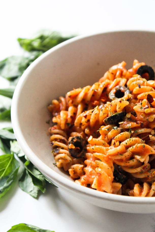 Red fusilli (spiral) pasta tossed in homemade tomato garlic pasta made with butter, garlic, tomatoes and cream cheese topped with olives. Served in a white bowl placed over a white tile.