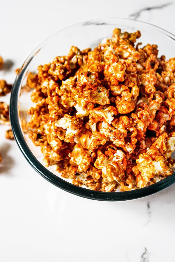 Golden brown crunchy and crispy popcorn coated with homemade salted caramel sauce in a glass bowl on a white tile.
