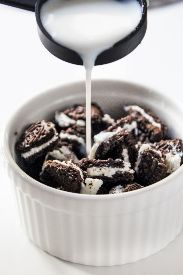 Broken/ Crushed Oreo Cookies in a white ramekin on a white tile and milk being poured on the oreo cookies.