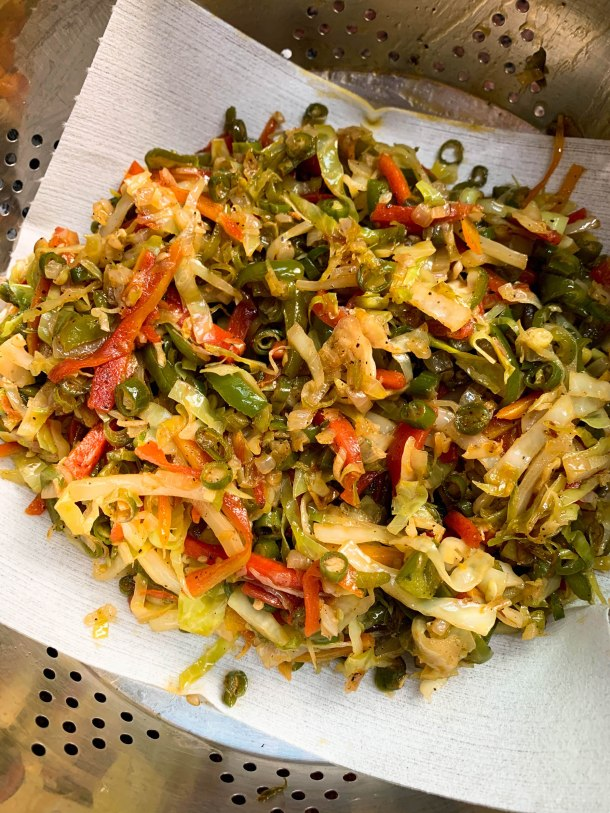 cooked shredded cabbage, carrots, capsicums and beans on a white kitchen paper