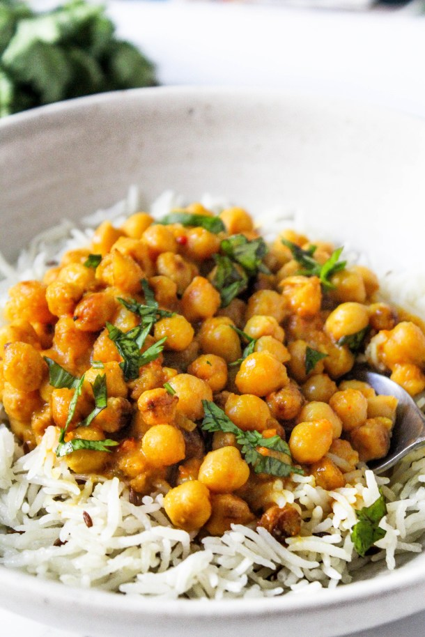 Brown chickpeas curry (made with coconut milk) topped with chopped green coriander, served over rice in a white bowl placed on a white tile.