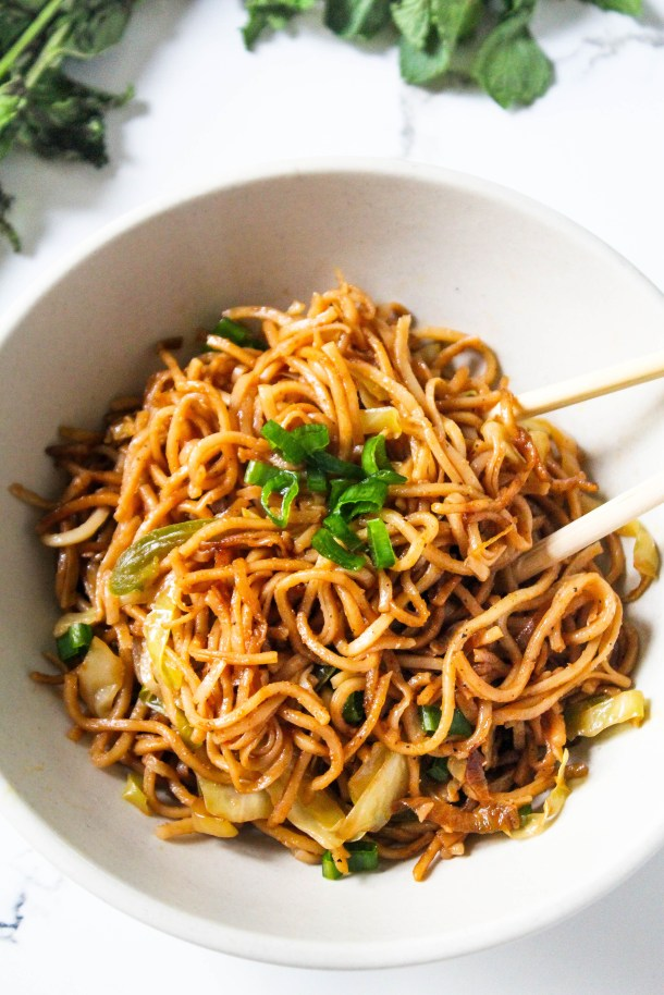 Hakka noodles in a dish placed on a white tile.
