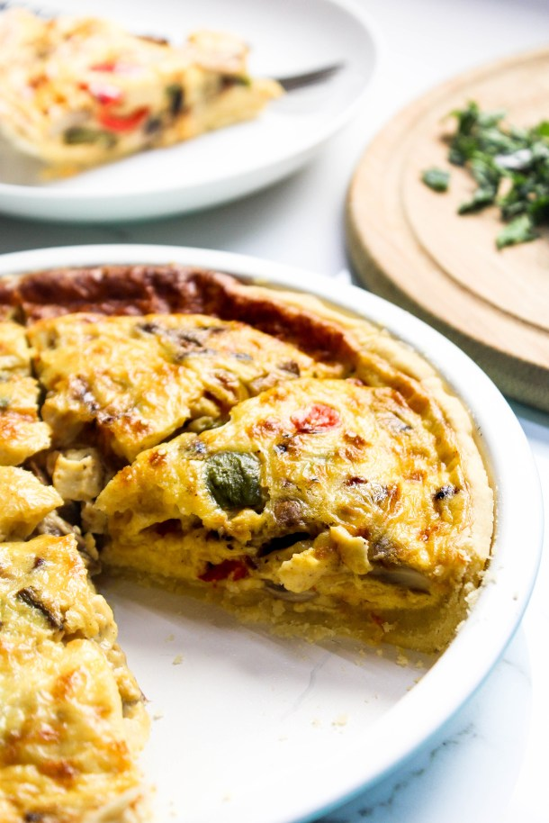 Homemade vegetarian quiche with mushrooms, peppers and onions in a pie dish.