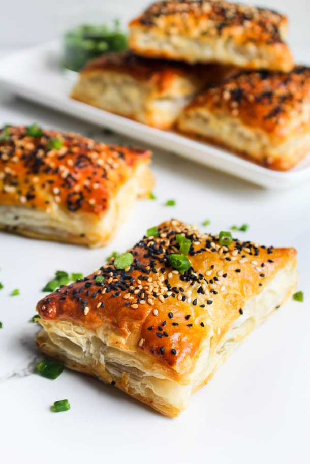 Flaky golden chicken puffs topped with sesame seeds, placed on a white serving plate over a white tile - garnished with chopped green spring onions.