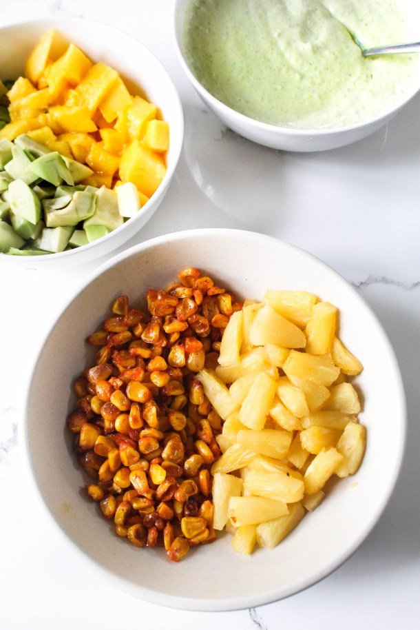cilantro jalapeño tangy mayonnaise ranch in a white bowl, roasted corn and pineapple in a white bowl and avocado and. mango chunks in a white bowl - all placed on a white tile.