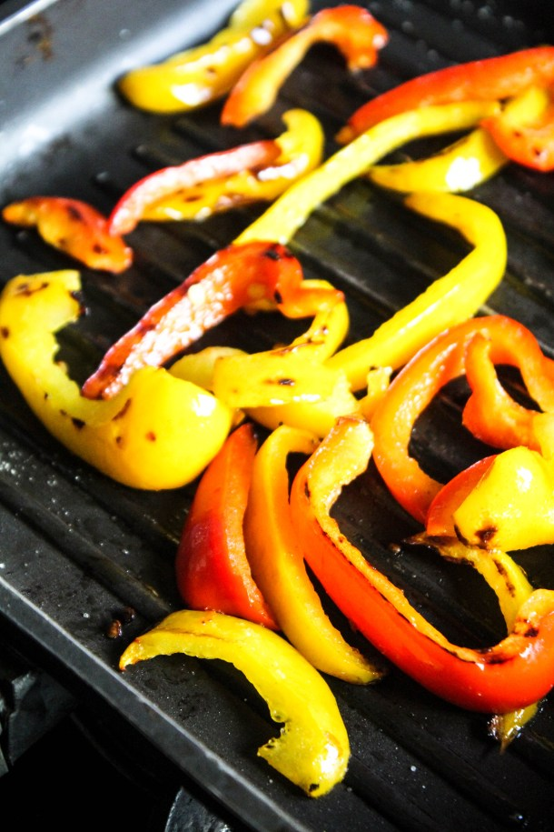 Red and yellow bell peppers on a black griller.