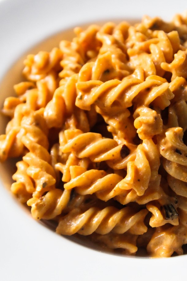 Creamy roasted red pepper fusilli pasta in a white plate placed on a white tile.